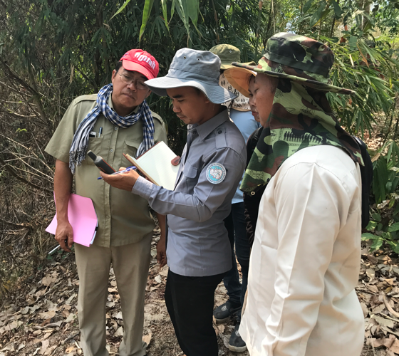 officials looking at a GPS in a tropical forest
